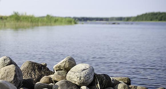 Stenar i förgrunden, Vänern i bakgrunden. Stämningsfull bild.