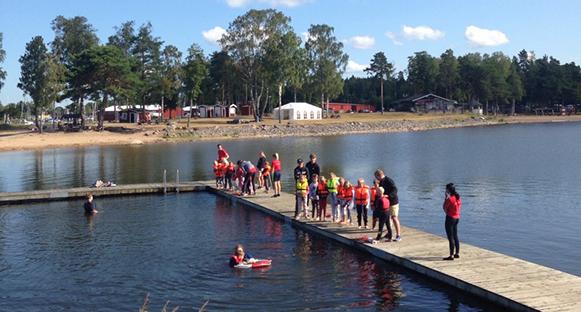 Hammarölägret 2019. Barn som står på bryggan vid Mörudden. Flytvästar på. Soligt väder. Ett barn simmar med räddningsringen.