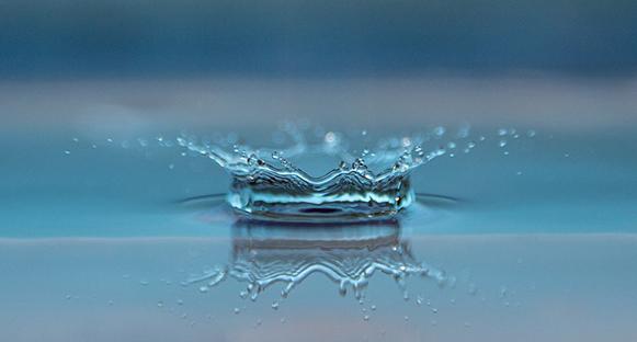 Närbild på en vattendroppe som landar på vattenytan.