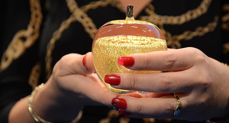 Guldäpplet som hålls av händer med långa röda naglar.