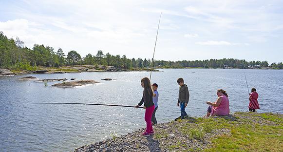 Barn som metar vid Vänerns strand.