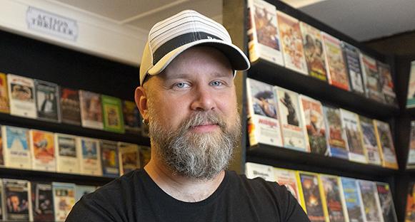 Fredrik Weileby stolt framför hyllor med VHS-filmer.