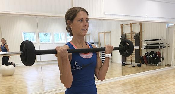 Veronica Ottosson håller en skivstång. I bakgrunden skymtas Therese Sundler balansera på knä på en pilatesboll.