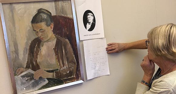 PRO på Clevegården har en tavla med en kvinna. Informationslapp bredvid tavlan. Någon står och läser på lappen.