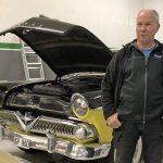 Jerry framför en jänkare i garaget. Motorhuven är öppen. Bilen är gul och svart.
