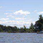 En ö med en båt vid brygga och liten sommarstuga. Bilden tagen på vägen ut mot Sööa från Mörudden.