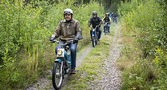 Äldre herrar som åker moped på skogsväg.