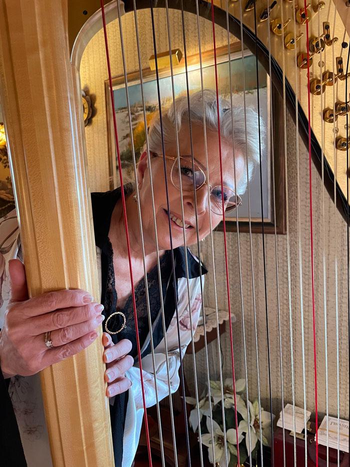 Gunilla står bakom och tittar fram genom strängarna på harpan.
